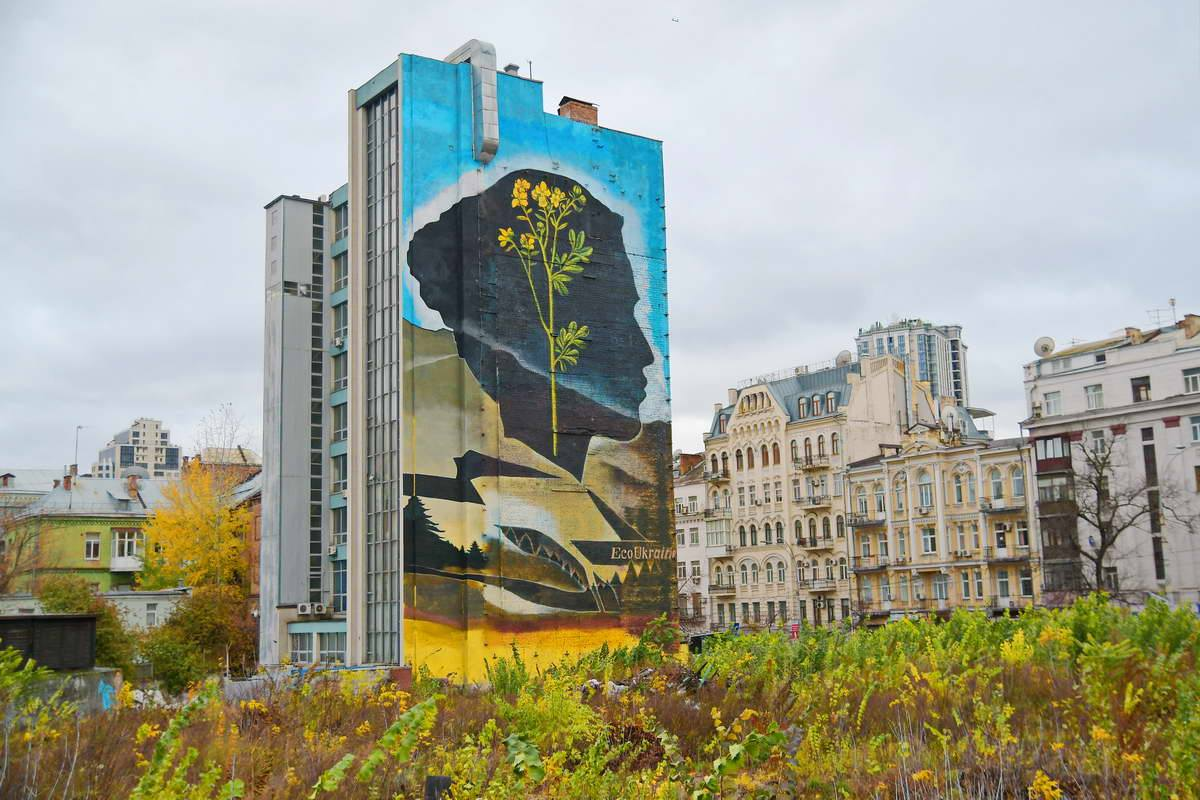 На фасаде здания прохожие видятчерный женский профиль с большим желтым цветком внутри