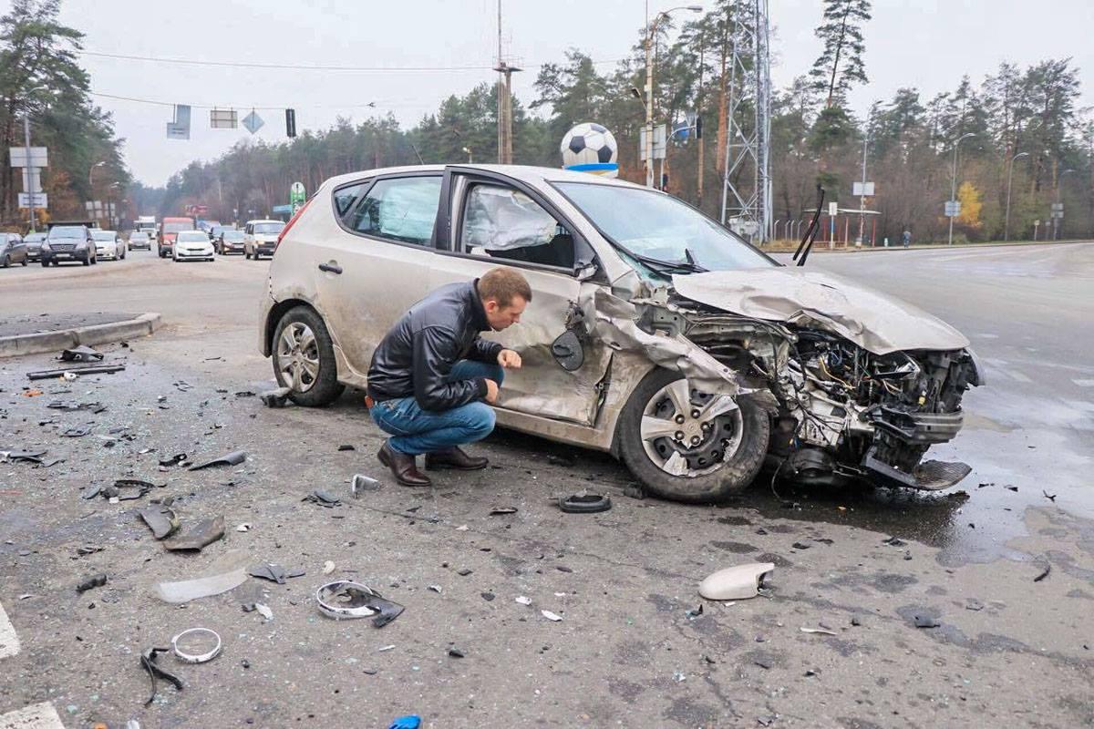 Владелец автомобиля осматривает повреждения