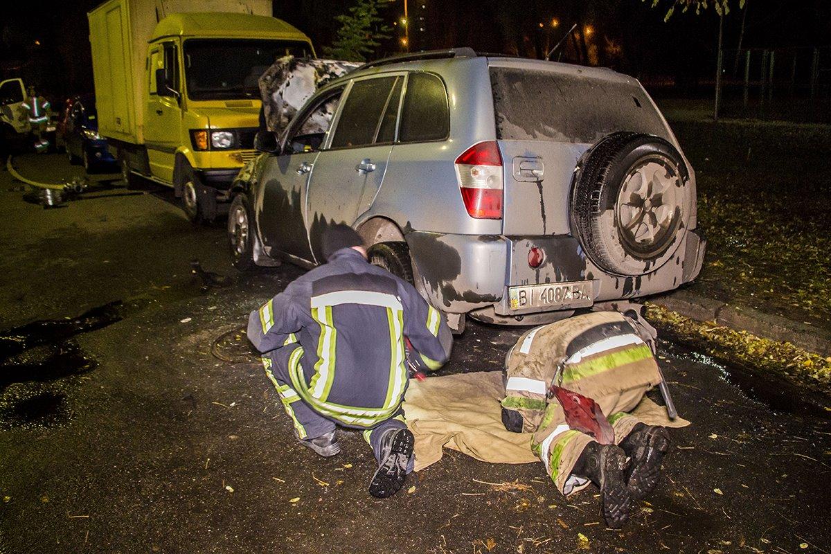Спасатели осматривают сгоревшее авто