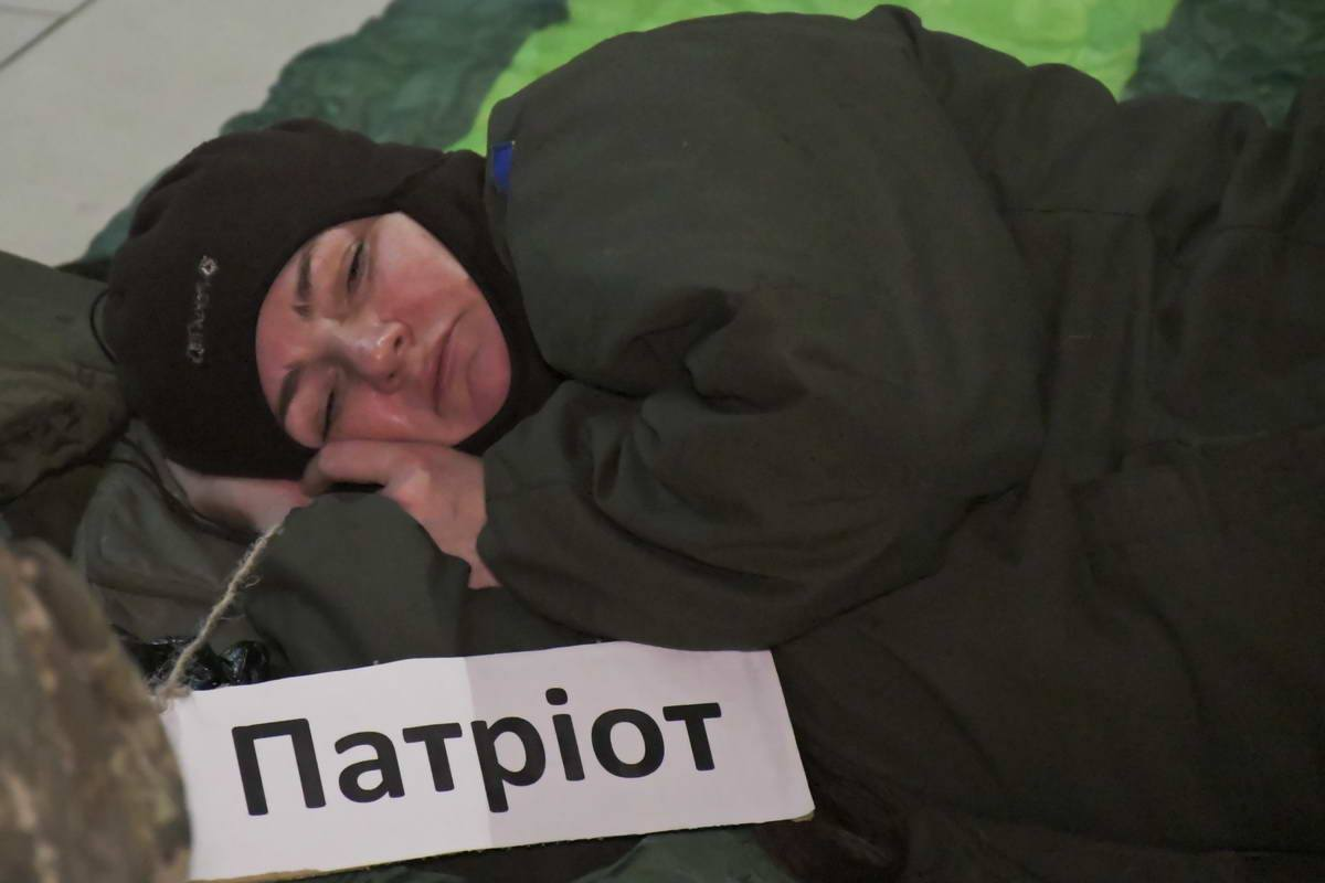 Кто-то из протестующих пытается уснуть на спальном мешке