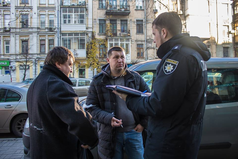 Главный представитель неизвестной группы мужчин пишет заявление на активистов