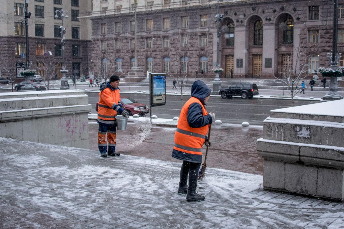 Коммунальщики убирают снег и посыпают тротуары специальной смесью