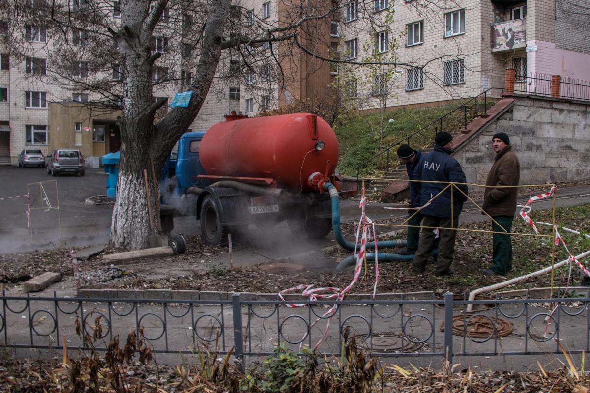 Они откачивают воду с канализационного люка, чтобы устранить повреждение трубы