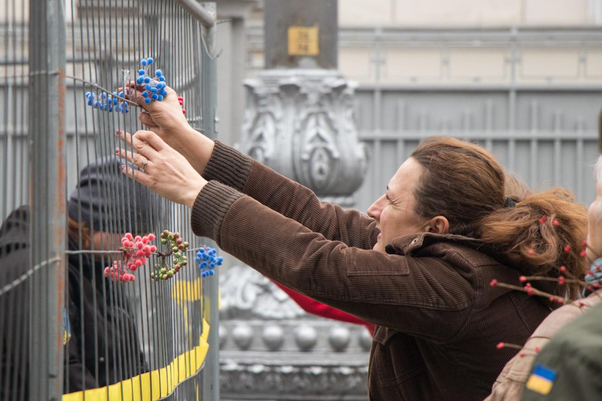 Женщина украшает ограду палаточного городка под Радой