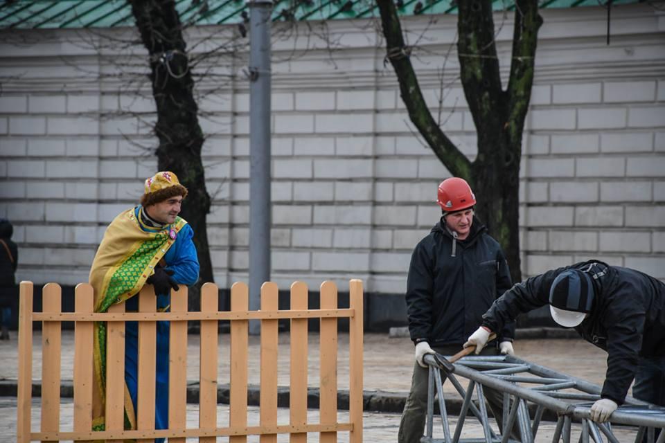 Мужчина морально помогает работникам устанавливать новогоднюю елку