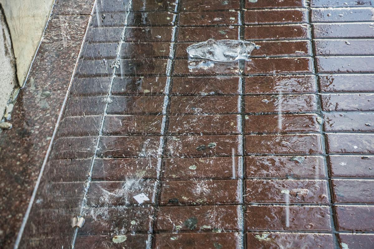 Маленькие льдинки лежат на асфальте, пока тоже не превратятся в воду