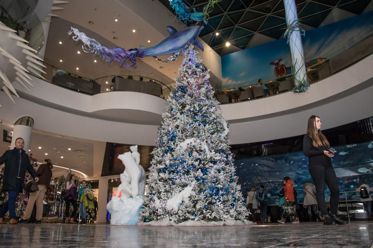 Бело-сине-серебристая елка радует посетителей у большого аквариума