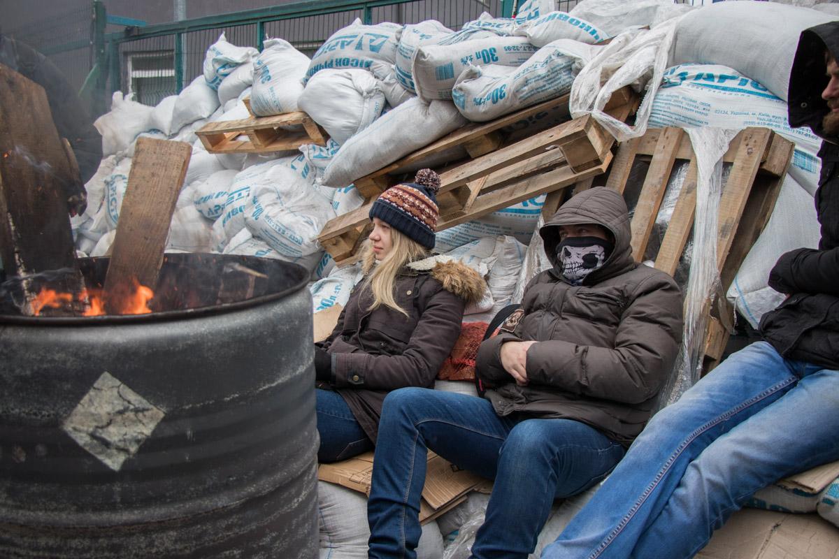 Активисты греются у огня, разведенного в бочке