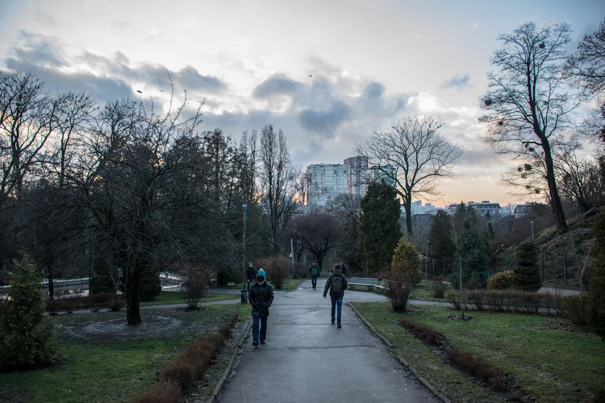 Смотря под ноги, идут по парку прохожие
