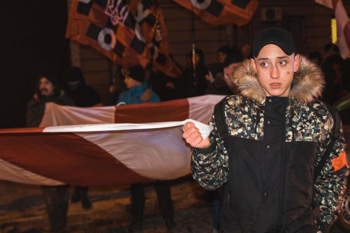 Участники марша несут флаг Беларуси