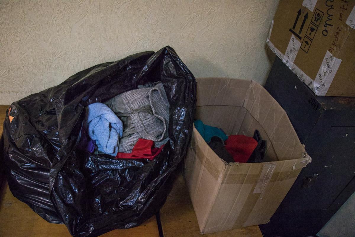 Одежда для бездомных здесь разложена в коробке и мусорном пакете