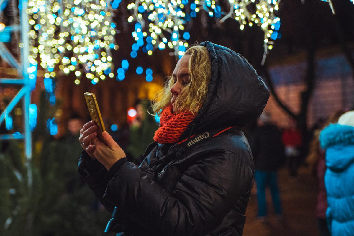 Люди спешат запечатлеть рождественские огни на камеру телефона