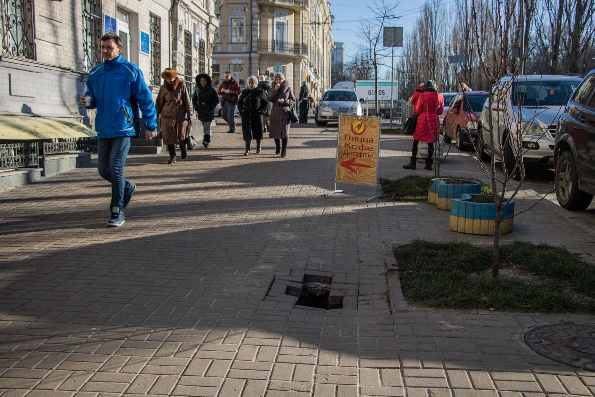 Люди обходят разрушение в тротуаре