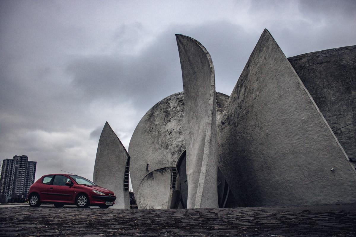 Игрушечные машинки теряются на фоне огромного строения