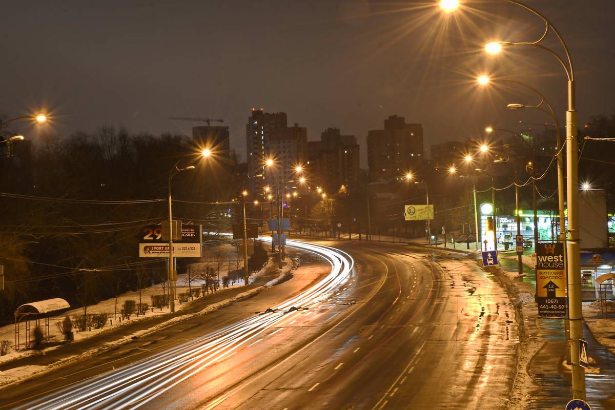 Пустынная автомагистраль, где только ночной свет фонарей летит на высокой скорости