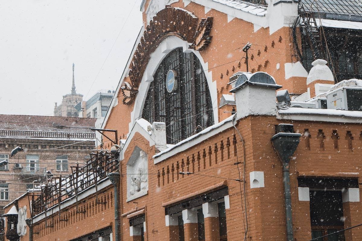Снежинки неспешно кружатся и опускаются на здания, покрывая его снежным покрывалом