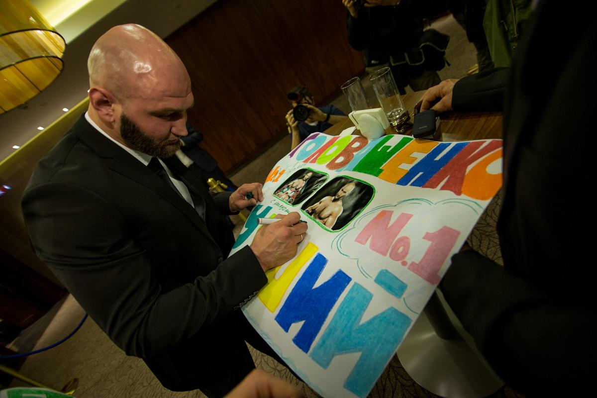 Фанаты принесли большие яркие плакаты, чтобы поддержать боксера
