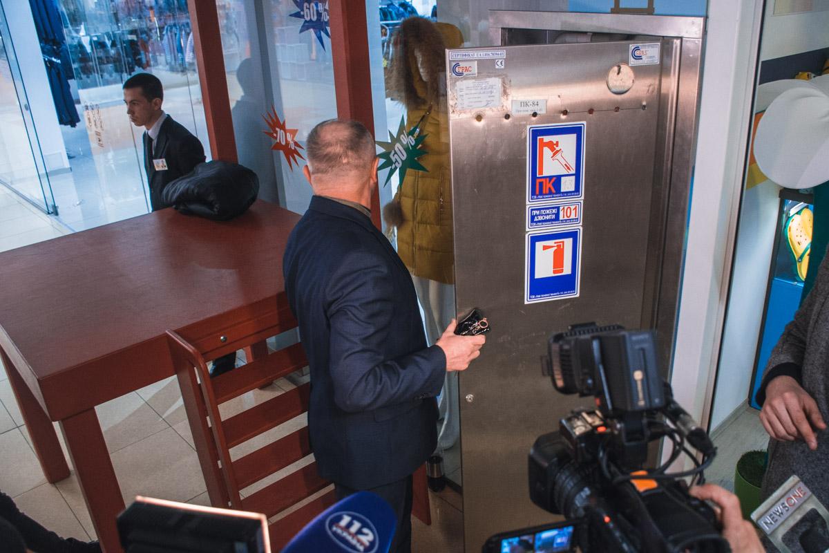 Начальник охраны показывает всем как отрываются шкафчики и срок годности баллонов