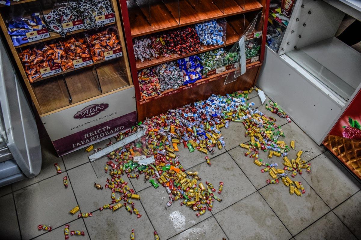 Конфеты и стекло разбросаны по всему полу магазина