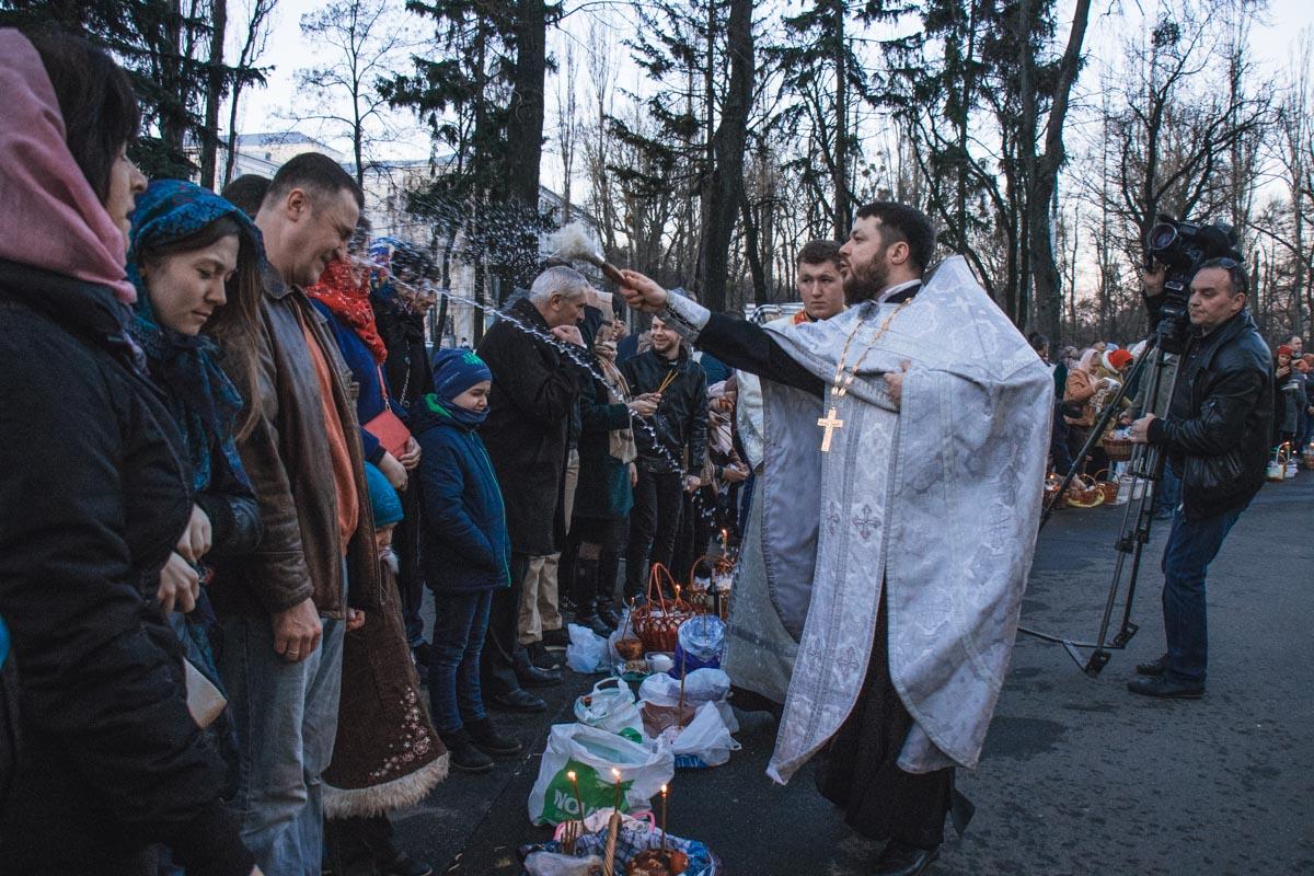 Батюшка щедро кропит жителей Киева святой водой