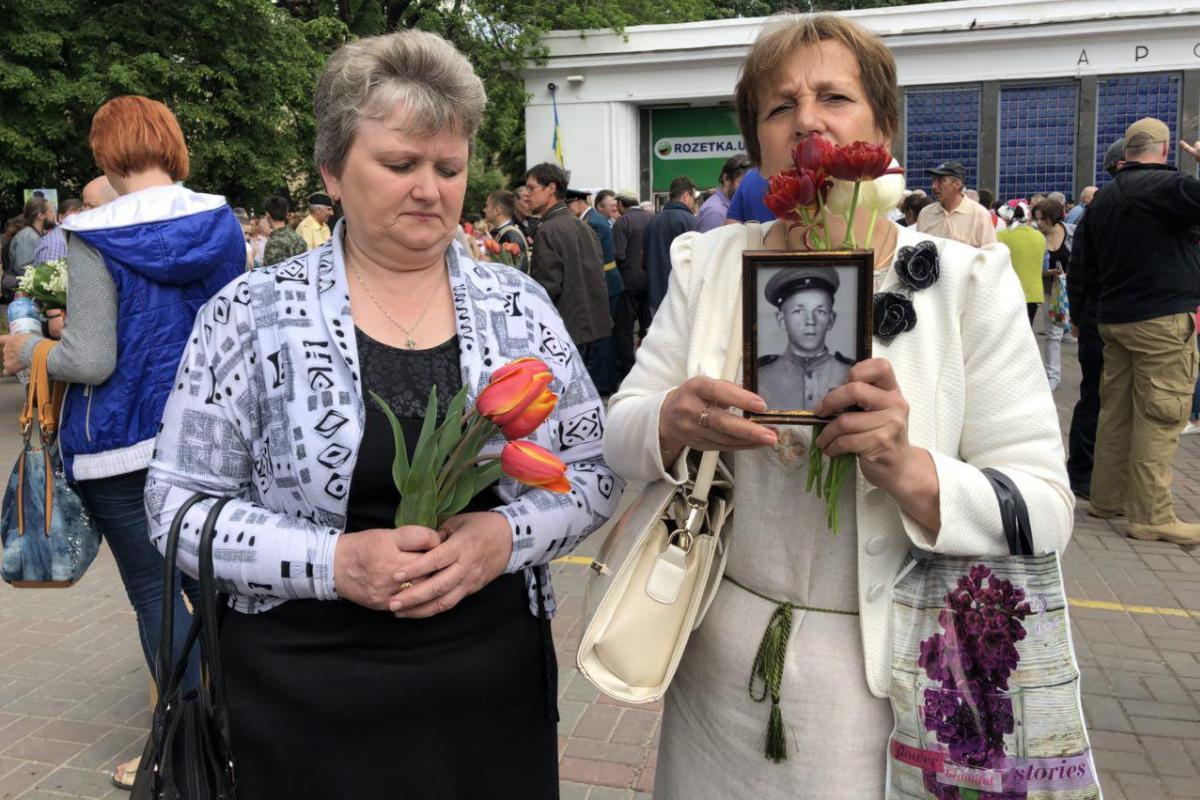 Пришедшие люди держат в руках фото своих родственников