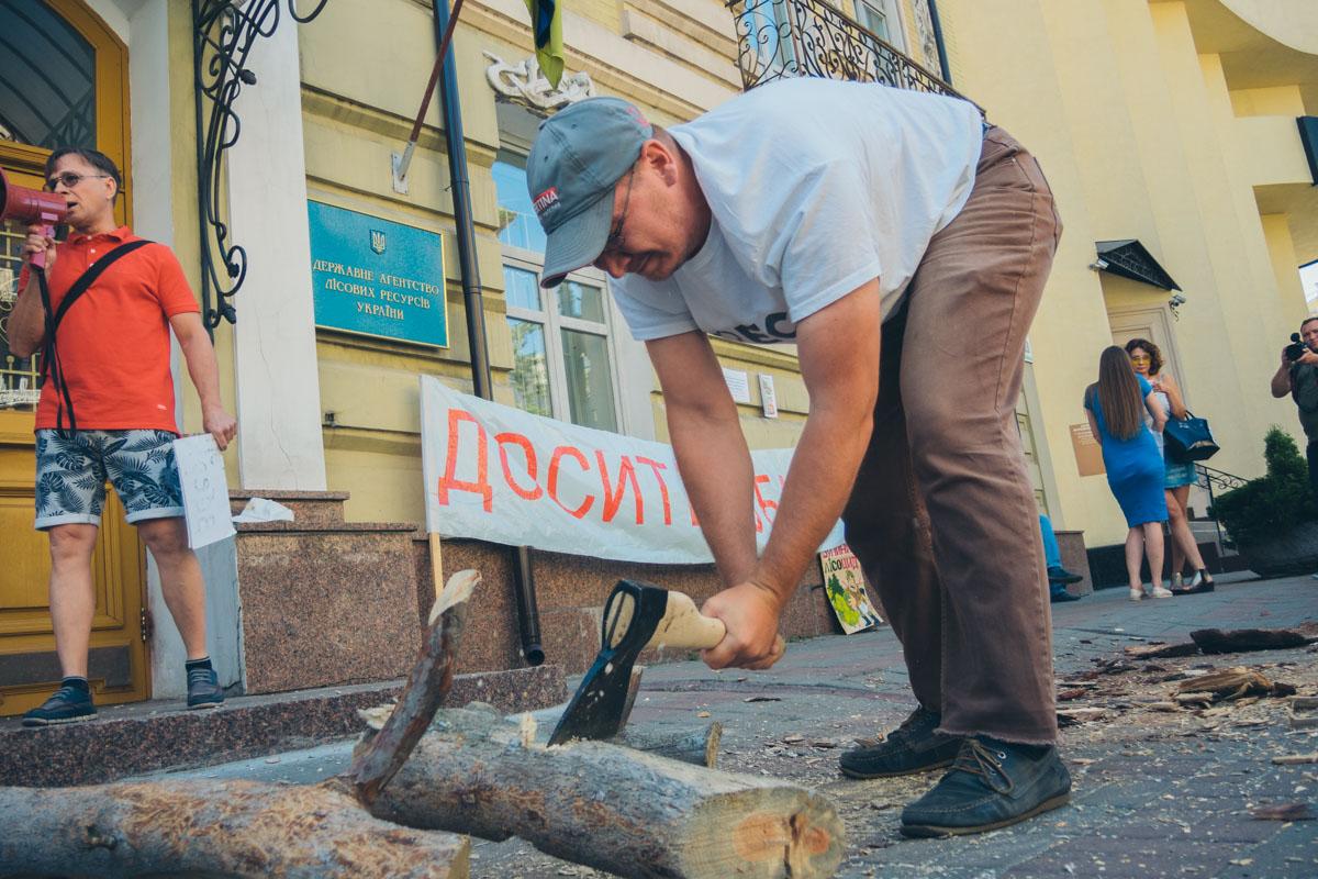 Участники митинга рубят дрова перед входом в агенство, чтобы привлечь внимание чиновников