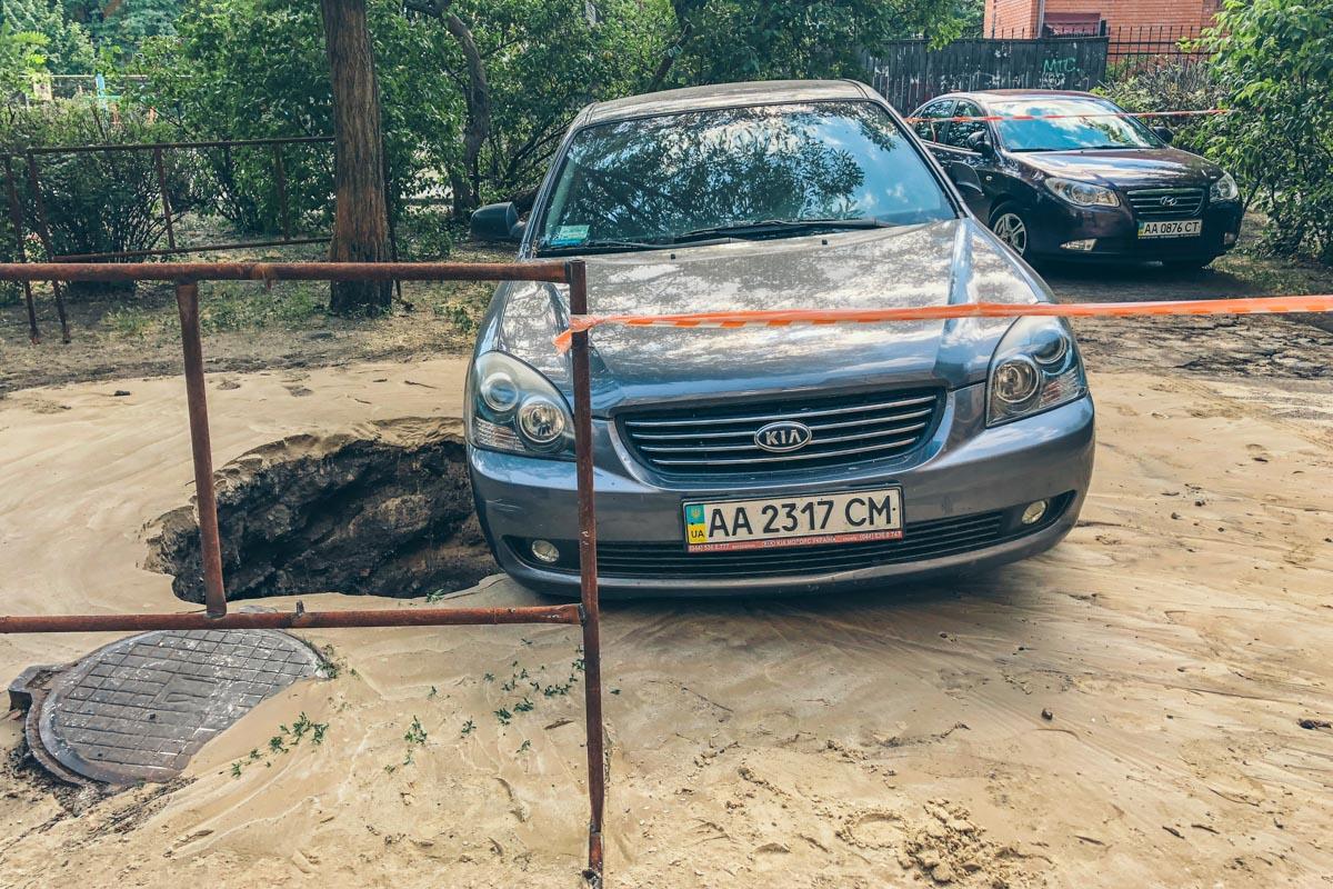 Автомобиль, припаркованный рядом, повис над 2-метровой ямой