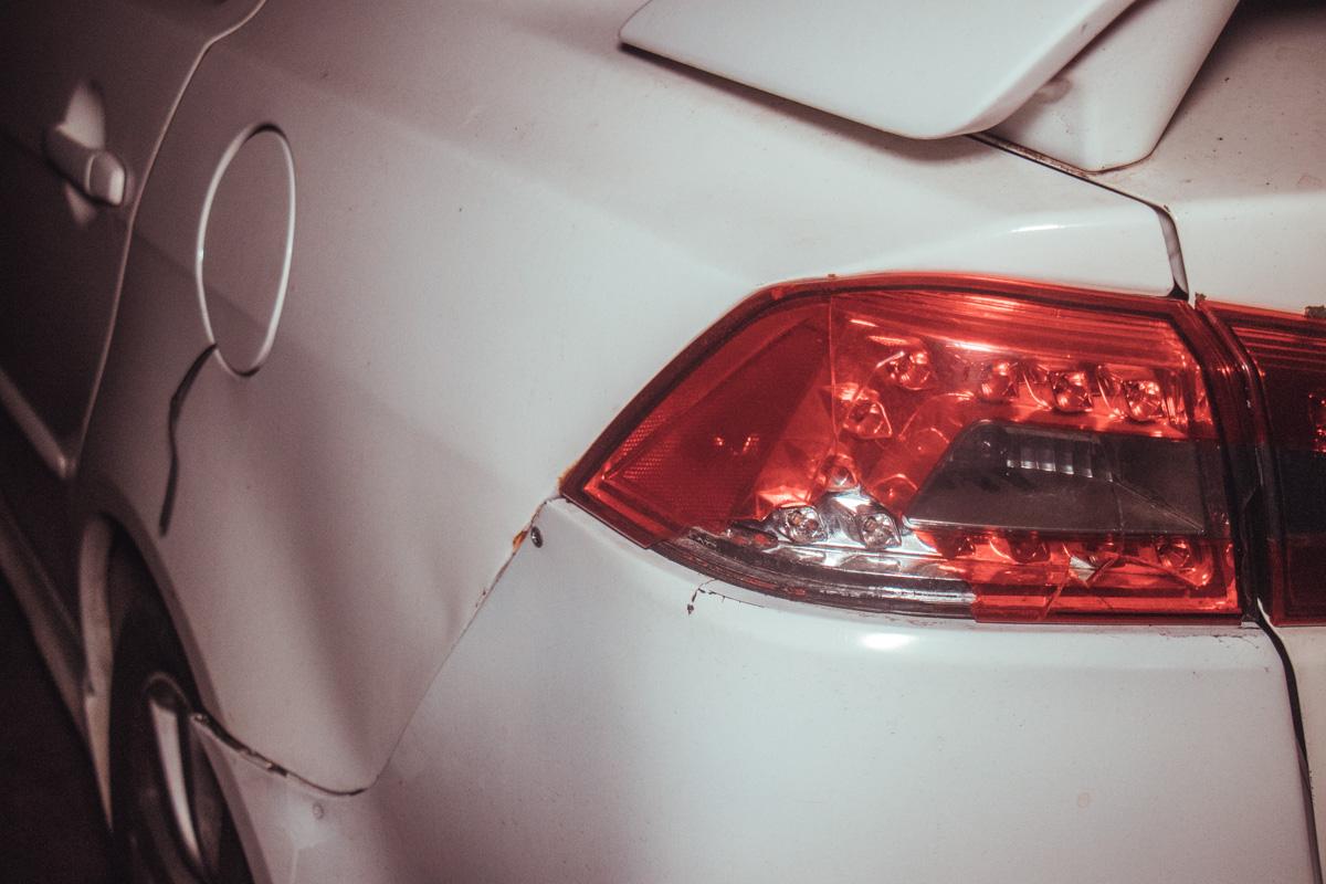 Вся машина в мелких вмятинах, криво стоит бампер и разбита задняя фара