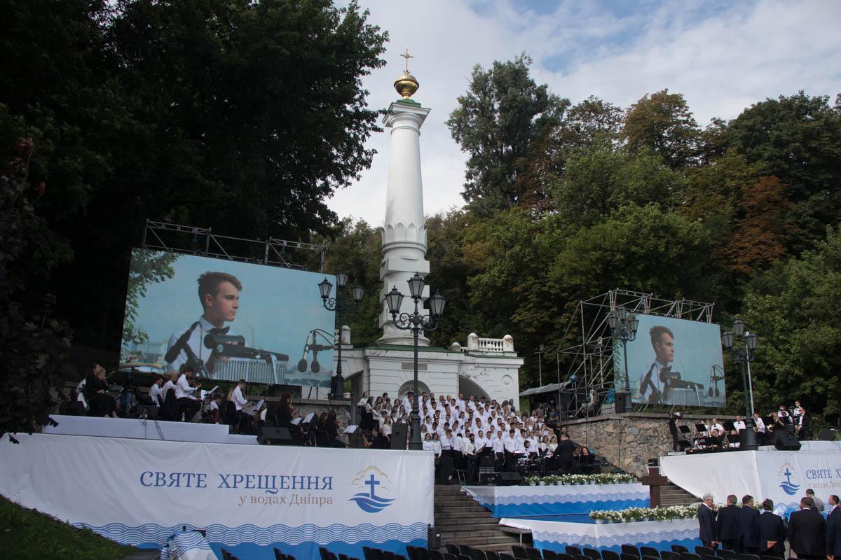 Служители церкви в белых одеяниях спустились по ступенькам от Владимирского спуска
