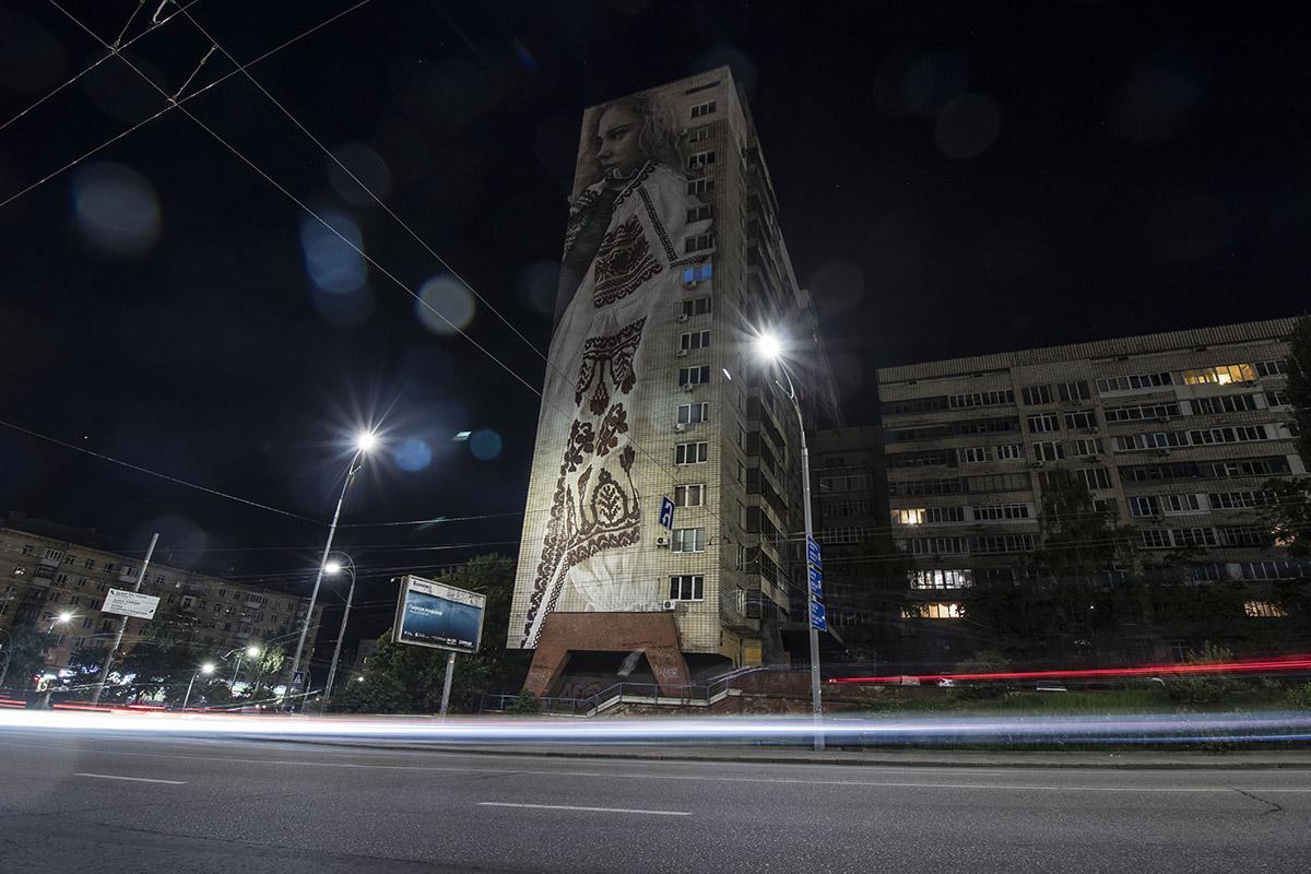 С огромного мурала девушка словно охраняет спокойствие ночного бульвара
