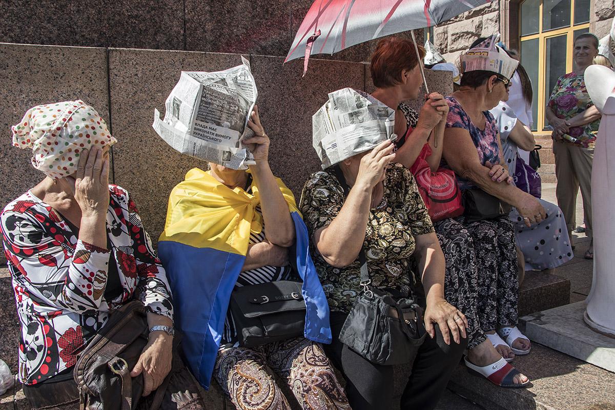 Участники акции прячутся от жгучего солнца кто как может