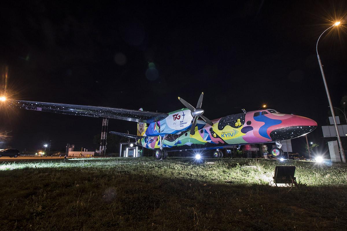 Яркий самолет в свете фонарей переливается новыми красками