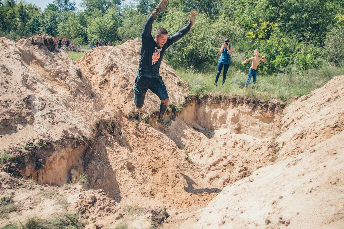 Спортсмены преодолевали ямы с песком, перепрыгивая препятствия