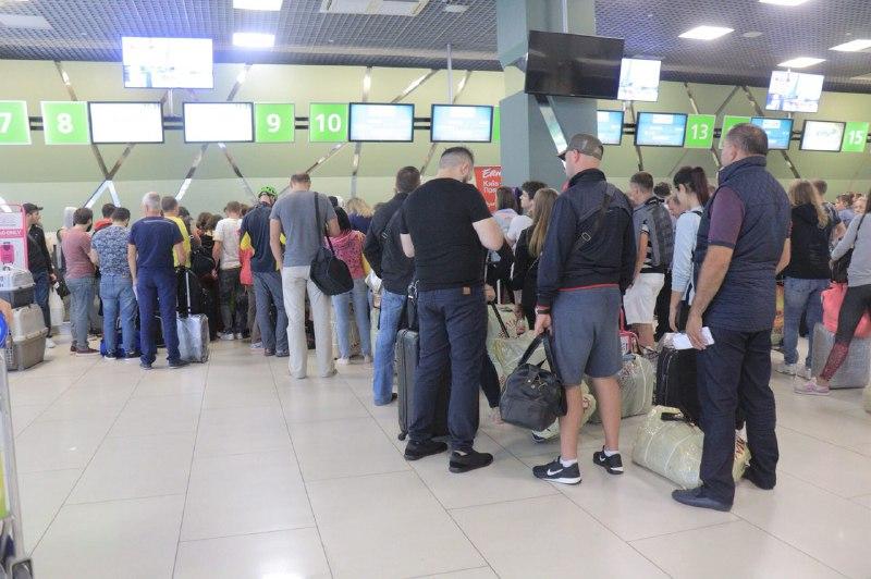 Люди толпятся в зале ожидания и у стоек регистрации