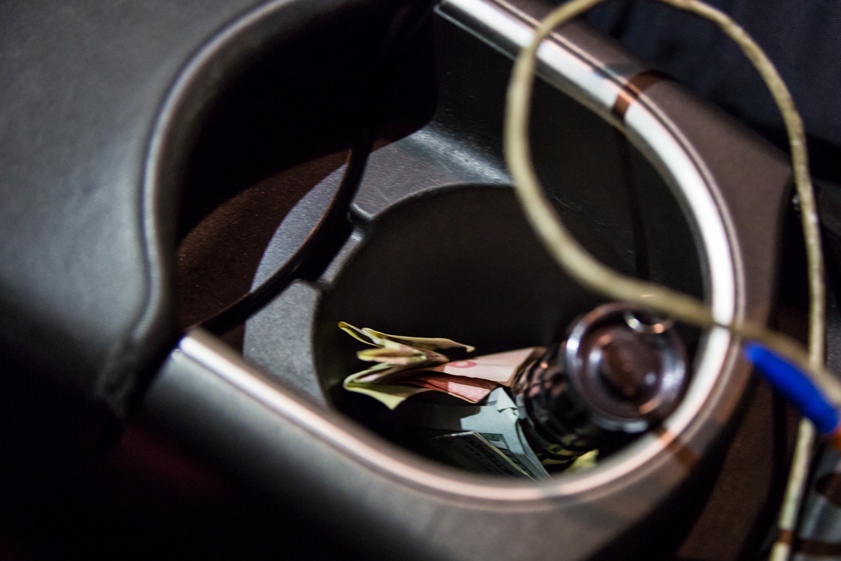 Водитель KIA подбросил три денежные купюры в подстаканник патрульной машины