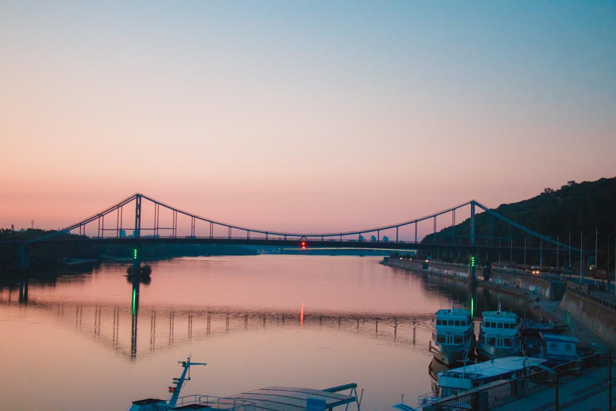 На рассвете мост волшебно отражается в воде