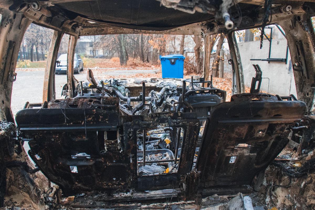 Дотла сгоревшая машина стоит на парковке здания, по какой-то причине у нее отсутствуют все четыре двери