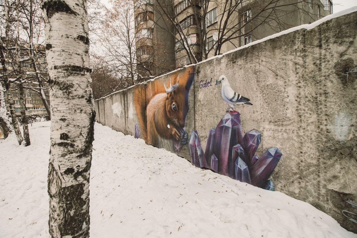 На невзрачном заборе на территории детского сада №680 по адресу улица Гродненская, 11А поселилась милая белочка с короной, которая грызет кристалл - аметист