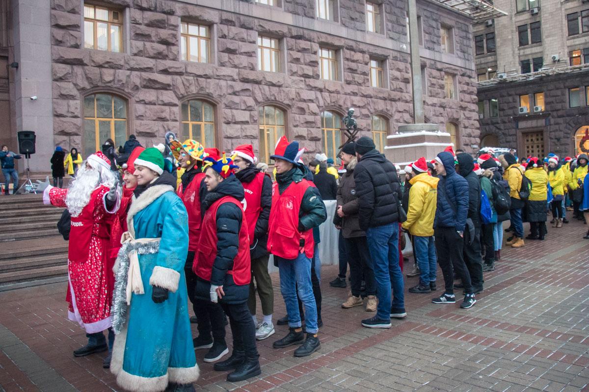 У здания КГГА собрались около сотни скаутов и волонтеров, которые поздравляли жителей и гостей столицы с Днем святого Николая