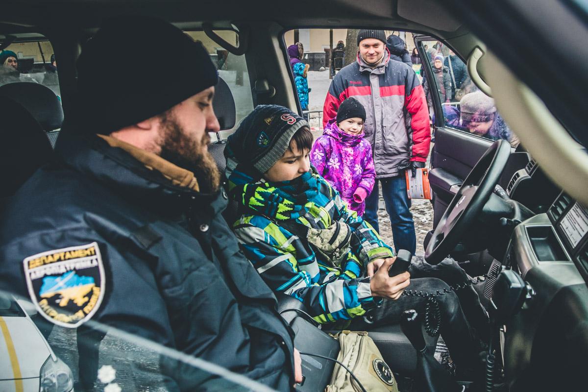 Патрульные катают маленьких детей на полицейских машинах с включенными мигалками и сиренами