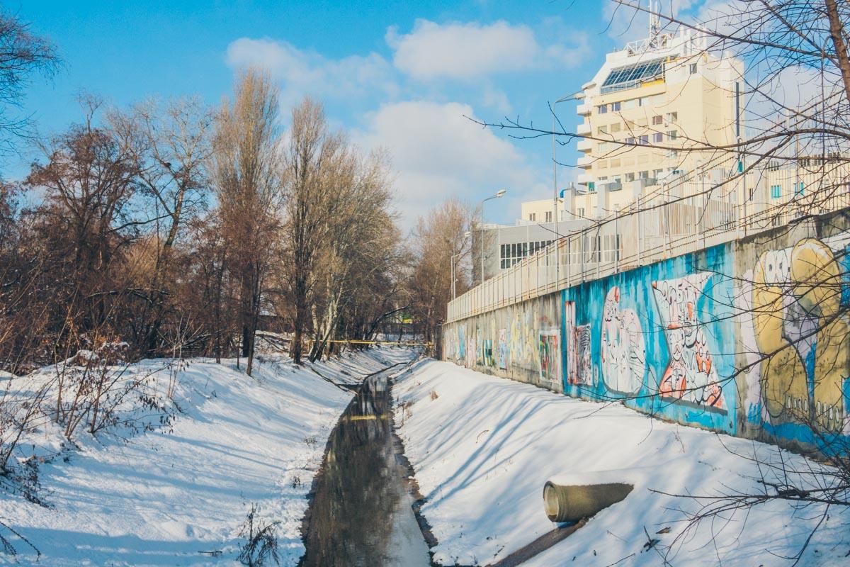 Территория ограждена старым высоким забором, на котором изображены десятки граффити