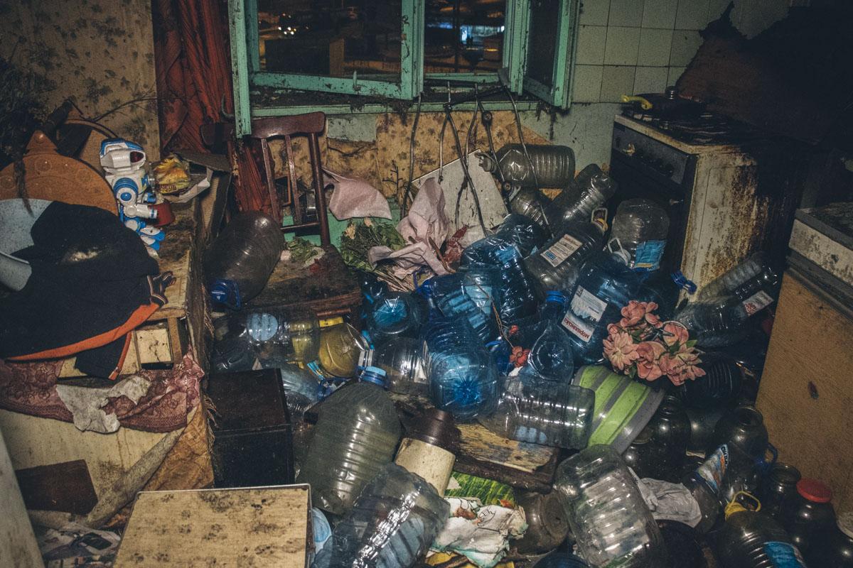 В заваленной мусором квартире из-за огромных долгов нет света и газа