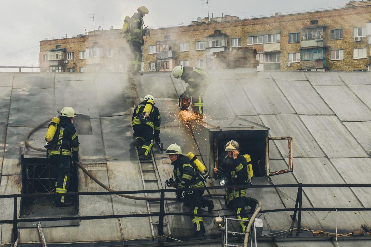 На чердак дома проход закрыт, это усложняет работу спасателей, с помощью бензореза они снимают с крыши листы профнастила, чтобы попасть внутрь