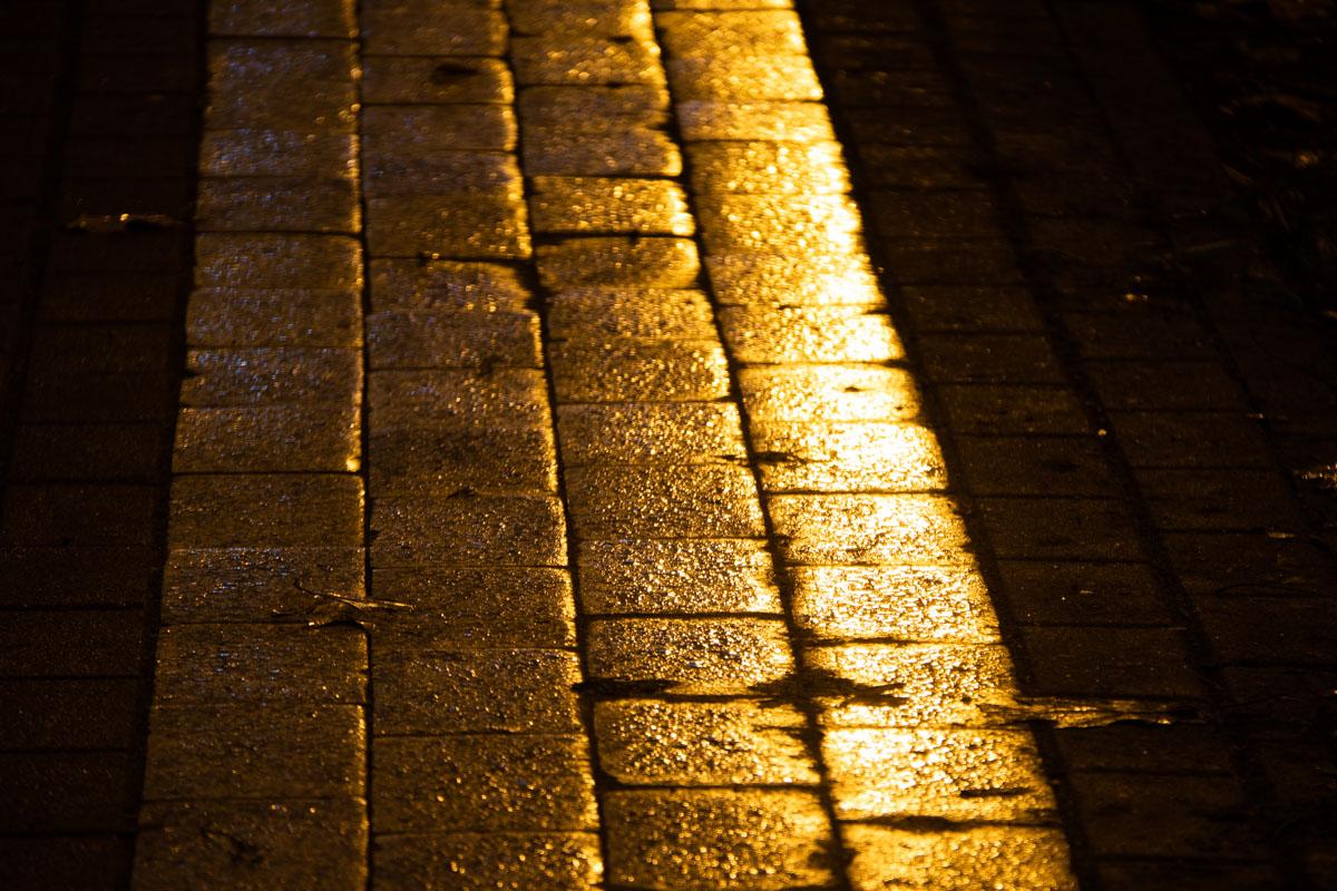 Мокрая плитка отражает свет ночных фонарей