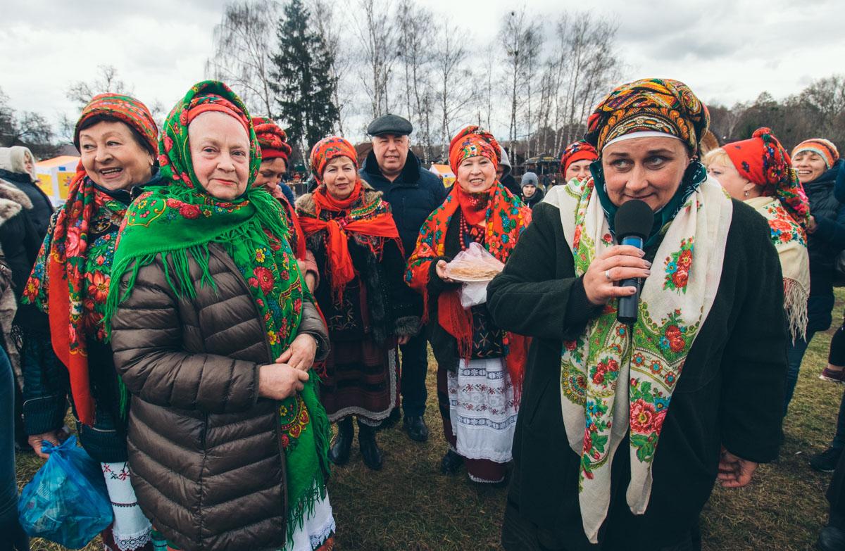 Женщины в украинских костюмах раздают гостям домашние пирожки и блины