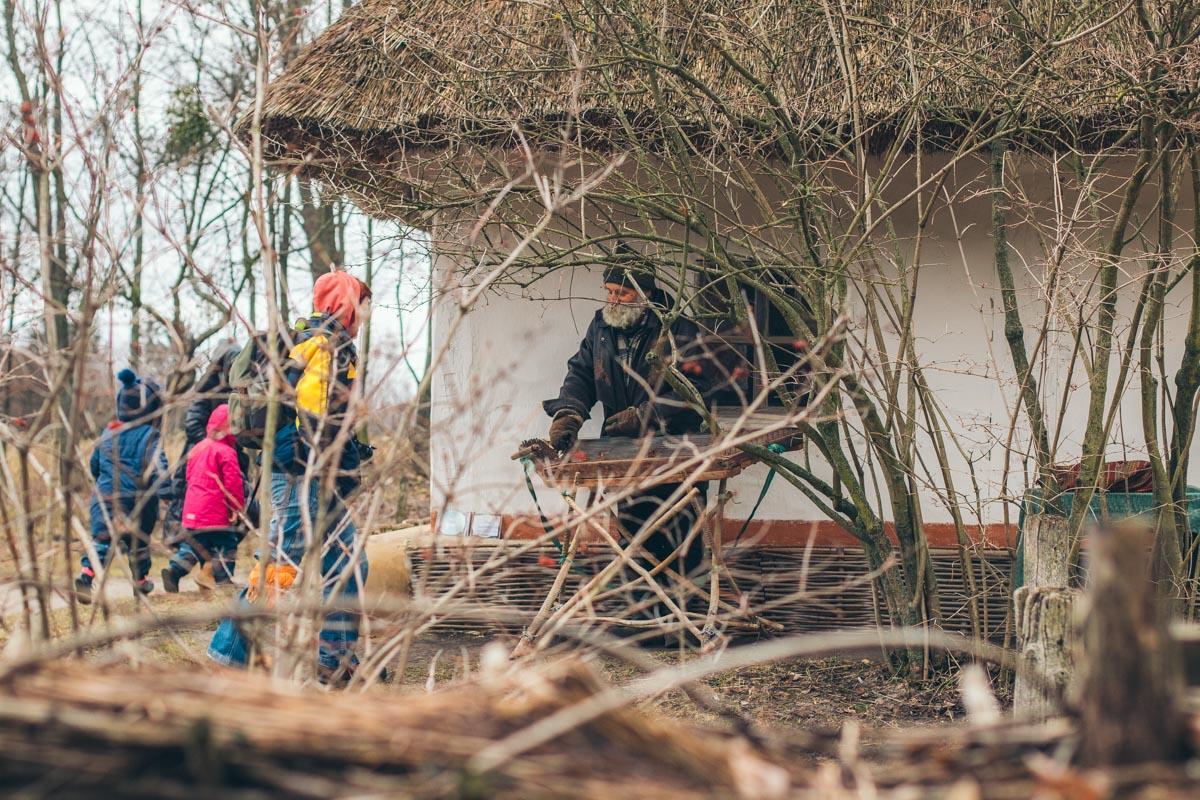Рядом со старинными домами с соломенными крышами добродушный старичок играет на цимбалах