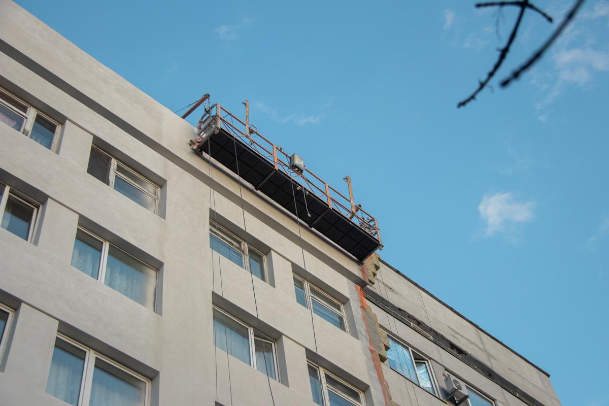 Бригада рабочих в составе троих человек, находилась в люльке на втором этаже здания