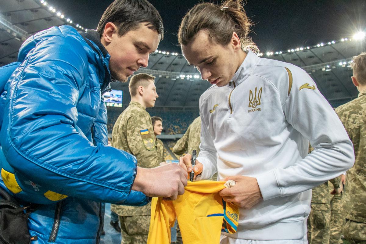 Николай Шапаренко оставляет свой автограф на футболке сборной. На ней уже расписалось немало сборников