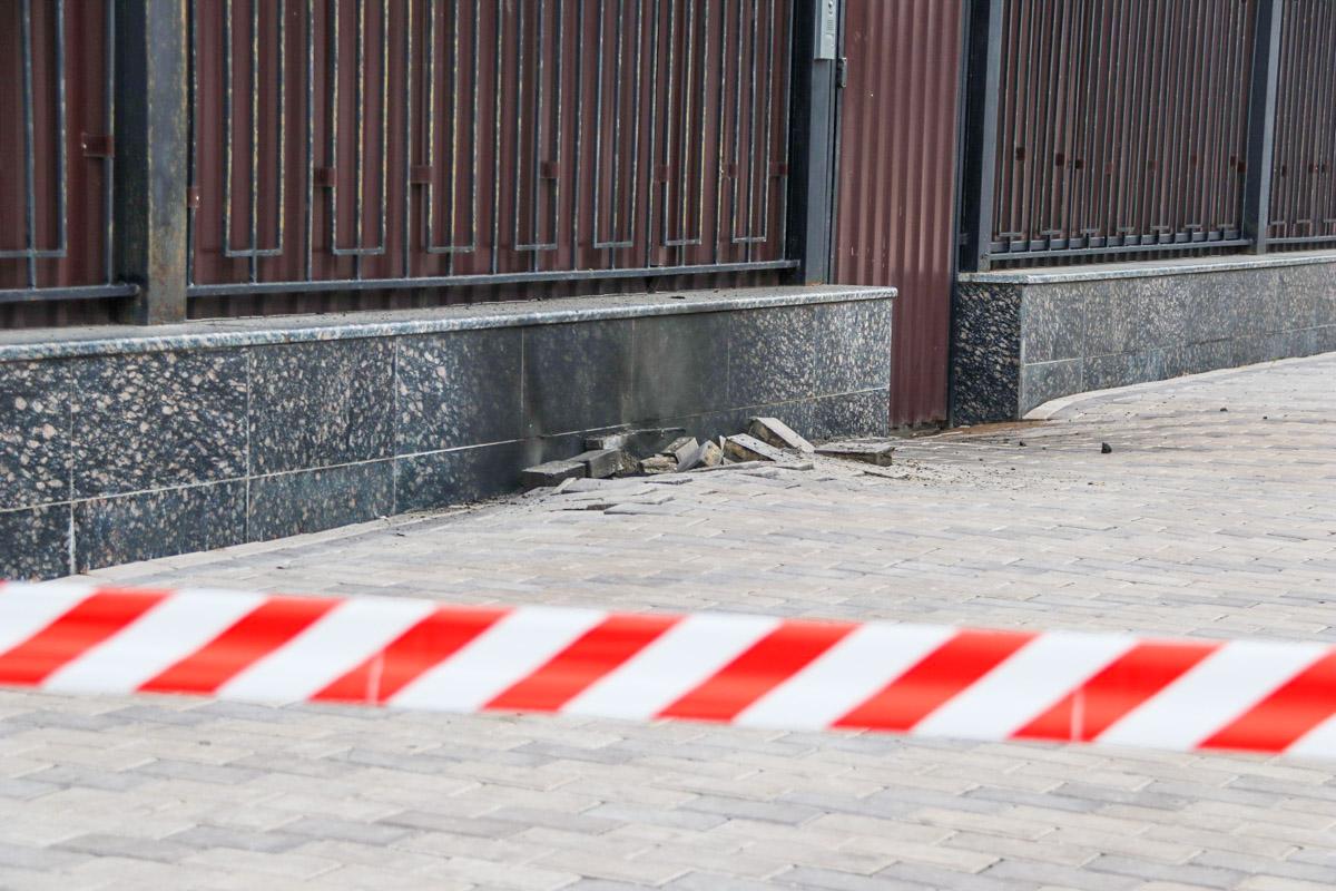 В результате взрыва была повреждена тротуарная плитка и появилось черное пятно на заборе