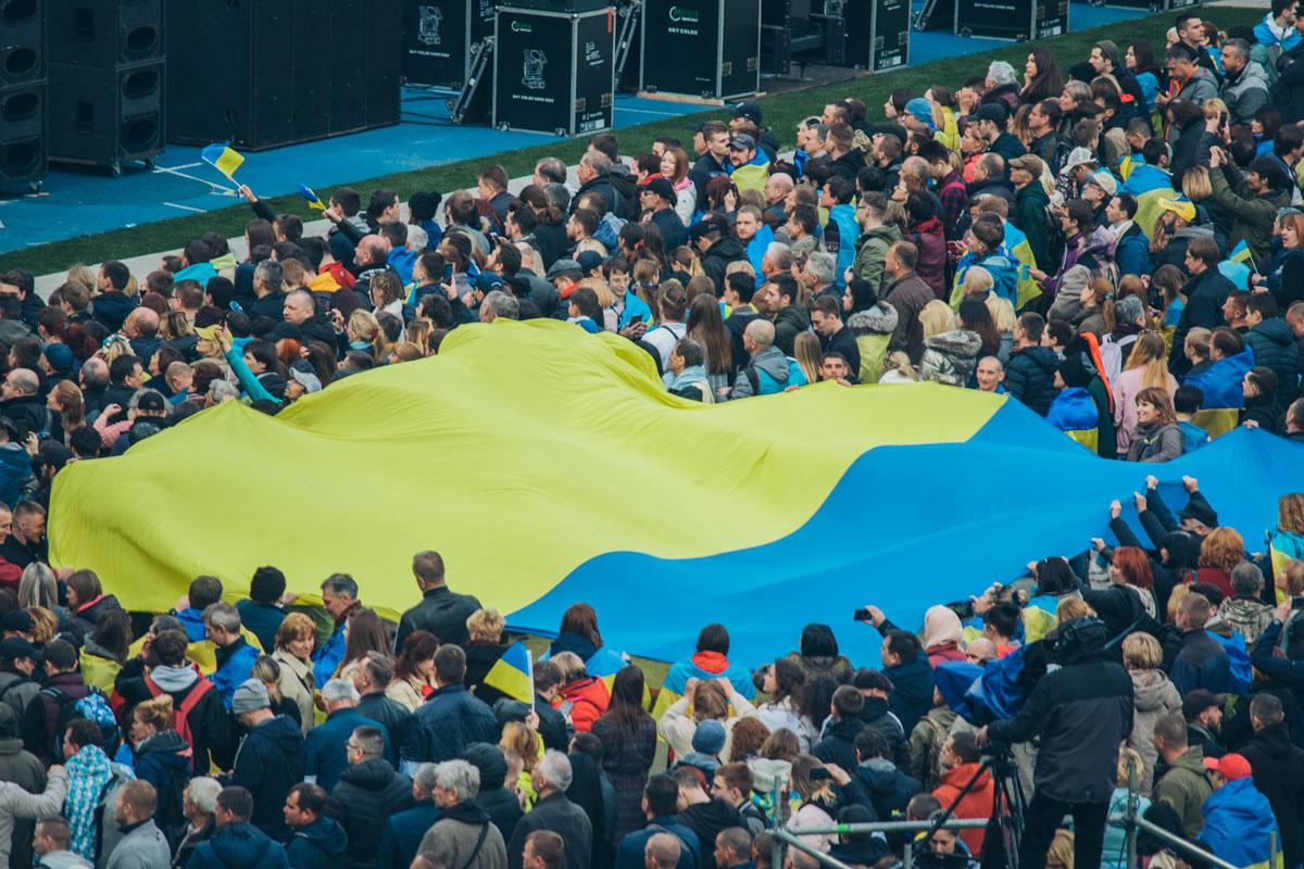 На стадионе собралась многотысячная толпа, растянув флаг Украины